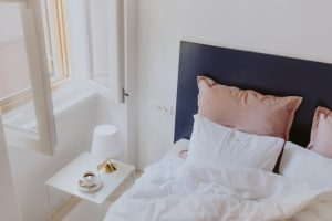 White-bedroom-interior-with-window-coffee-and-small-lamp-on-side-table