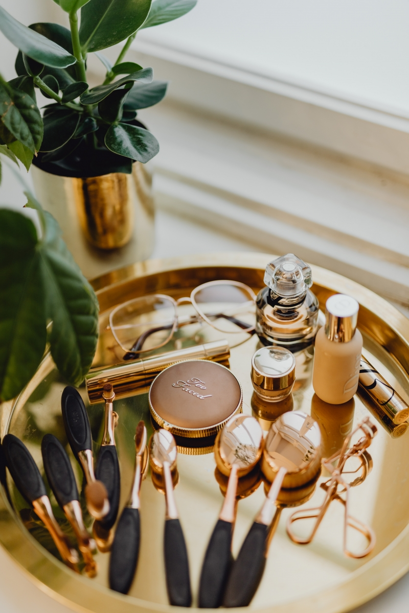 Makeup essentials on a golden tray