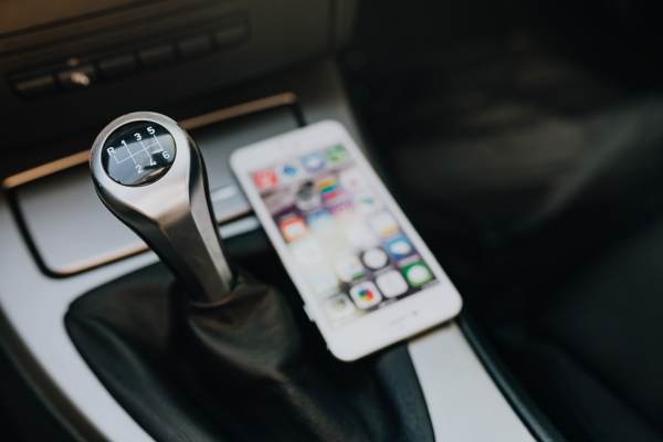 Modern car interior with smart phone on manual gear stick