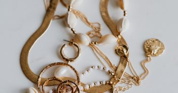 Gold jewellery on white marble - necklace, bracelets, earrings