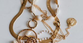 Gold jewellery on white marble - necklace, bracelets, earrings